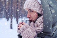 Starke Frau, die eine Schale mit einem heißen Tee beim Betrachten hält Stockbild