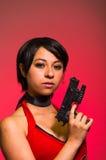 Starke Frau, die schlechtes cosplay Residentkostüm der Gewehr-Actionfilm-Art hält Stockfotografie