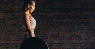 Starke Frau, die schwere Gewichte an der Turnhalle anhebt stockfotografie