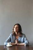 Starke Frau, die zuhause nahe Tasse Kaffee sitzt Stockfotografie