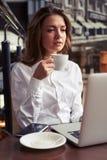 Starke Frau mit Tasse Kaffee vor Laptop Lizenzfreie Stockbilder