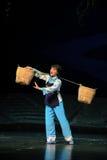 Starke Frau trägt eine schwere Belastung Jiangxi-Oper eine Laufgewichtswaage Stockfotografie