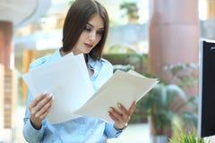 Starke Geschäftsdame, die Dokumente im Büro vergleicht lizenzfreies stockbild
