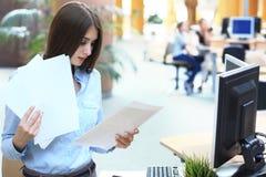Starke Geschäftsdame, die Dokumente im Büro vergleicht stockbilder