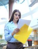 Starke Geschäftsdame, die Dokumente im Büro vergleicht stockbild
