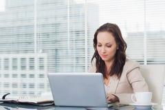 Starke Geschäftsfrau, die an ihrem Laptop arbeitet Lizenzfreie Stockbilder