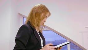 Starke Geschäftsfrau, die mit Dokument im Büro nahe Fenster arbeitet stock video