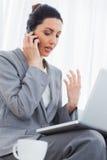 Starke Geschäftsfrau, die mit ihrem Handy nennt und den Laptop sitzt auf Sofa verwendet Stockbild