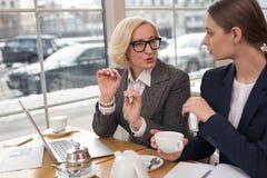 Starke Geschäftsfrau, die neues Projekt mit ihrem Partner bespricht Stockfoto