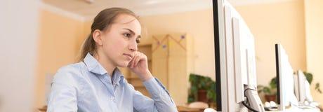 Starke Geschäftsfrau, die versucht, eine schwierige Aufgabe auf Linie in einem Tischrechner im Büro zu lösen stockfotos
