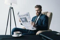 Starke Geschäftsmannlesezeitung im Büro Stockfotografie