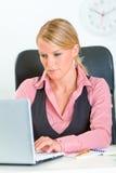 Starke Geschäftsfrau, die am Büroschreibtisch sitzt Stockfotografie