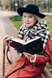 Starke grau-haarige Frau, die auf ihrem Spazierstock sich lehnt stockbilder