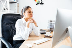 Starke intelligente Geschäftsfrau, die Bildschirm betrachtet Stockfoto