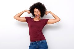 Starke junge afrikanische Frau, die beide Armmuskeln biegt und auf weißem Hintergrund blinzelt Stockbilder
