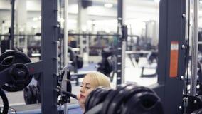 Starke junge blonde Frau mit schönem athletischem Körper in der schwarzen Ausstattung, die untersetztes Training mit Barbell in d stock footage