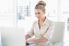 Starke junge blonde Geschäftsfrau, die einen Laptop verwendet Stockbilder