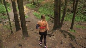 Starke junge Frau, die hinunter Forest Trail And Going Down vom Hügel läuft stock video