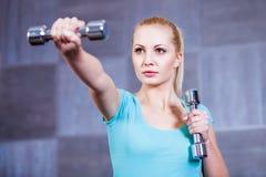 Starke junge Frau, die mit Dummköpfen an der Turnhalle trainiert Stockfotografie