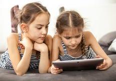 Starke junge Mädchen, die digitale Tablette verwenden Lizenzfreie Stockfotografie