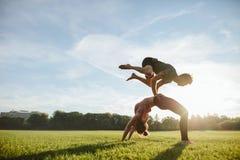 Starke junge Paare, die acroyoga Training tun Stockbilder