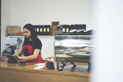 Starke Kellnerin, die schwer in der zeitgenössischen Kaffeestube arbeitet Stockfotos
