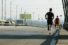 Starke L?ufer, die auf Stadtbr?ckenstra?e laufen Laufen auf Stadtstra?e Marathonlaufen morgens Athletenl?ufer-Fu?betrieb stockfotografie