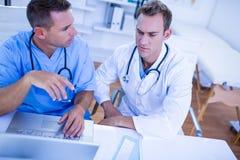 Starke medizinische Kollegen, die mit Laptop sich besprechen und arbeiten Stockbild
