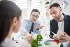 Starke Mitarbeiter, die ihr Projekt besprechen lizenzfreies stockbild