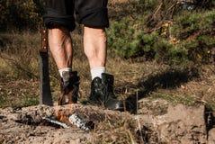Starke musculine Beine eines Mannes, staning in der halben Drehung hinter Feuer lizenzfreies stockbild