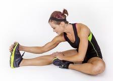 Starke muskulöse Frau, die vor Training auf weißem Hintergrund ausdehnt Lizenzfreies Stockfoto