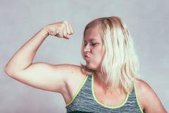 Starke muskulöse sportliche Frau, die Bizeps biegt Stockbilder