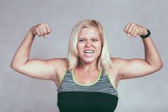 Starke muskulöse sportliche Frau, die Muskeln biegt Lizenzfreie Stockfotos
