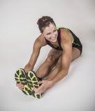 Starke muskulöse Frau, die vor Training auf weißem Hintergrund ausdehnt Lizenzfreie Stockfotos