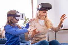 Starke Mutter und ihr Kind, die VR-Kopfhörer trägt Lizenzfreie Stockfotos
