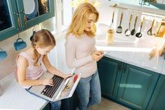 Starke Mutter und Mädchen, das moderne Geräte verwendet Stockfoto
