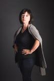 Starke, reife dunkelhaarige Frau, die mit den Händen auf Hüften steht Stockfotos