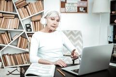 Starke reife Frau, die Schirm des Laptops betrachtet lizenzfreie stockfotografie