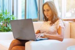 Starke schöne Frau, die einen Laptop beim Sitzen im bequemen weißen Innenraum verwendet Weibliche Freiberufler-Funktion Lizenzfreies Stockfoto