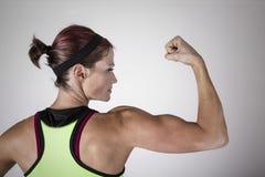 Starke schöne Eignungsfrau, die ihren Arm und Rückenmuskulatur biegt Stockfotografie