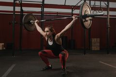 Starke Sportfrau, die Hocken mit schweren Barbellunkosten an der crossfit Turnhalle tut lizenzfreies stockfoto