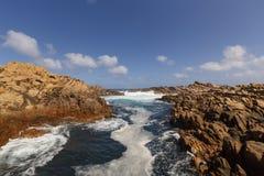 Starke Strömung des Wassers hetzend durch die Felsen an der Küste Lizenzfreie Stockbilder