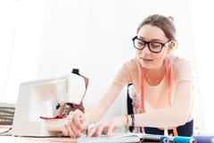 Starke tragende Gläser der Frauennäherin, die in der Werkstatt stehen und arbeiten stockbild