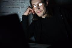 Starke tragende Gläser des Mannes unter Verwendung der Laptop-Computers lizenzfreies stockbild
