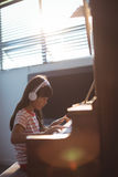 Starke tragende Kopfhörer des Mädchens beim Üben des Klaviers durch Fenster Stockbilder