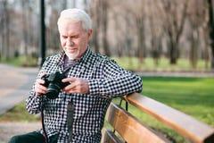 Starke verschlingende Fotografieinformationen des reifen Mannes lizenzfreies stockbild