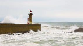 Starke Wellen brechen über den Pier, den Leuchtturm auf dem Ufer des Atlantiks stock video