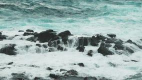 Starke Wellen des Ozeans gliedern auf den Küstenfelsen auf stock footage