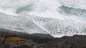 Starke Wellen, die in felsige vulkanische Küstenlinie rollen Verlassener schwarzer Sandstrand auf Trekkingsspur auf Santo Antao I stock footage