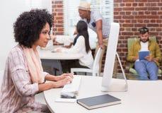 Starke zufällige Frau, die Computer verwendet Lizenzfreies Stockbild